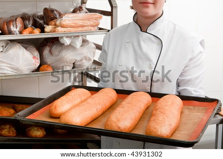 Young cook  shows fresh-baked bread and cakes - stock photo