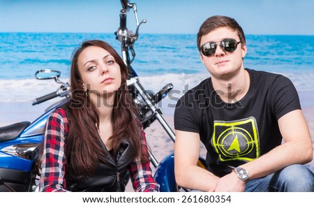 Young Cool Couple Looking Tough Crouching in front of Motorcycle on Beach #261680354
