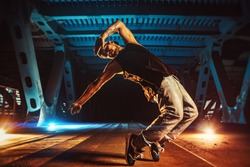 Young cool man break dancer on urban bridge with cool and warm lights background. Tattoo on body.
