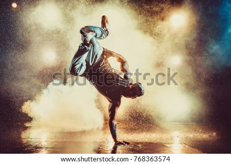 Photo of Young cool man break dancing in club with lights, smoke and water. Tattoo on body.