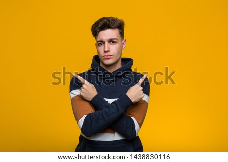 Young cool man wearing a hoodie points sideways, is trying to choose between two options.