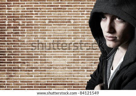 Young cool street style fashion male model posing at brick wall