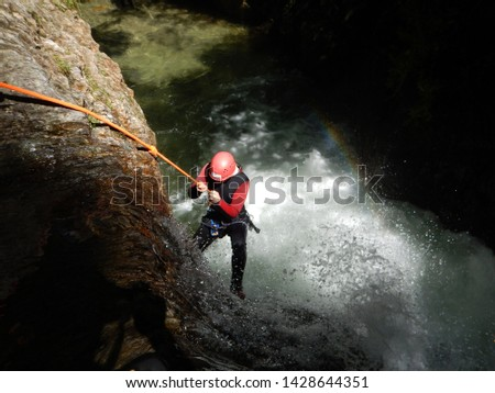 young corageous girl climbing down while canyoning - rappeling into the water in the canyon Photo stock ©