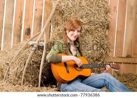 Young country woman sitting on hay play guitar in barn