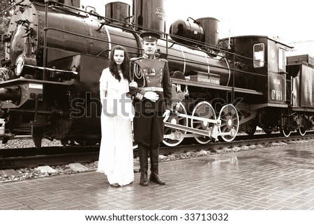 Young coupe in oldfashion dresses infront of old engine