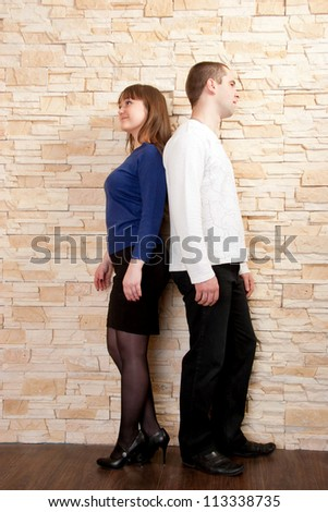 Young couple - a boy and girl standing back to back against a brick wall. Quarrel, dispute, compromise search