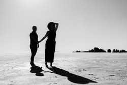 young couple a guy and a girl with joyful emotions in black clothes walk through the snow white desert