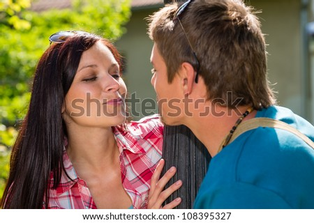 Young couple about to kiss on sunny day in park