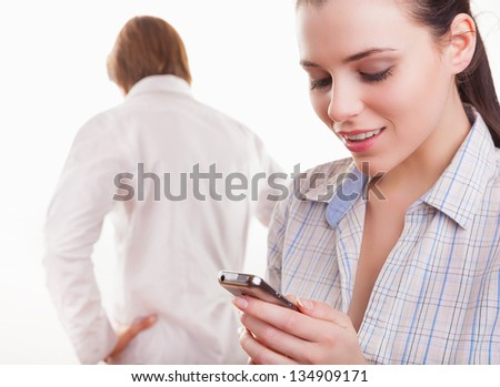 Young couple after quarrel. Woman looking with a smile on your phone in the foreground