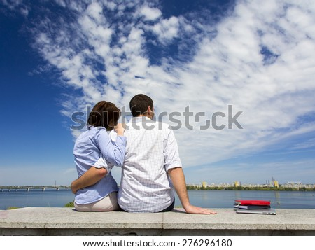 Young couple and cloudy sky. Two people male and female sitting on railing embracing in front of urban view with river and blue sky clouds