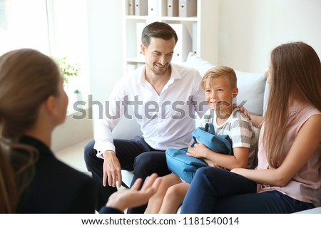 Young couple and their son meeting with headmistress at school