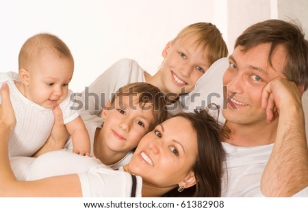 young couple and their sons on a white