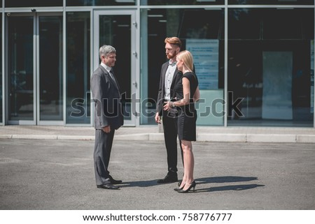Young couple and vehicle manager standing outside auto showroom. Man and woman talking with sales manager.