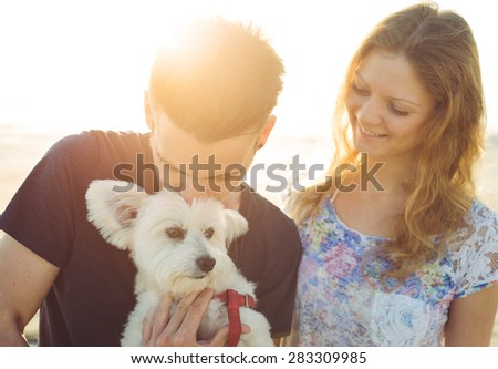 young couple and white dog happily together. couple taking a morning walk with their dog. concept about couples,animals and people