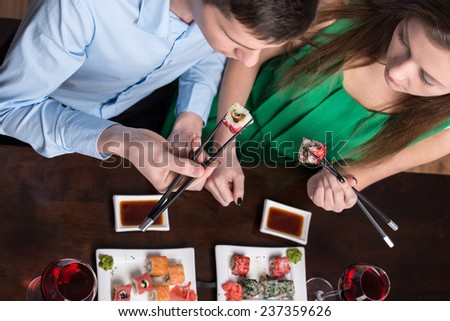 Young couple are eating sushi at restaurant. Top view.