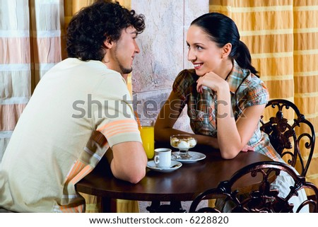 Young couple are sitting at the table and looking at each other