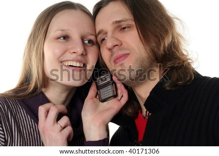 Young couple are talking by one mobile phone together happy