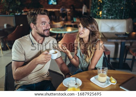 Young couple arguing while sitting and drinking coffee in restaurant