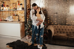 Young couple at home in the kitchen on Christmas time near Christmas tree. Man hug his woman from back.