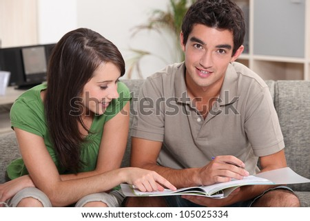 young couple at home skimming through catalogue