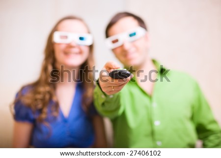 Young couple at home watching movie in 3D glasses. Focus on remote control.