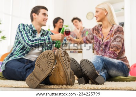 Young couple at house party with faces out of focus in the foreground are the soles of their shoes, sit on the floor, knocking the toasting glasses, in the background you can see another couple.