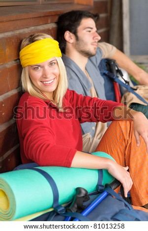 young couple backpack relax sitting by wooden cottage