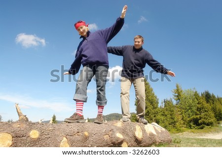 Young couple balancing on cut wooden log