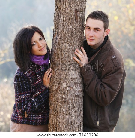 Young couple behind a tree an autumn - stock photo