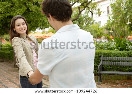 Young couple being playful in a park while on holidays in a Mediterranean destination.