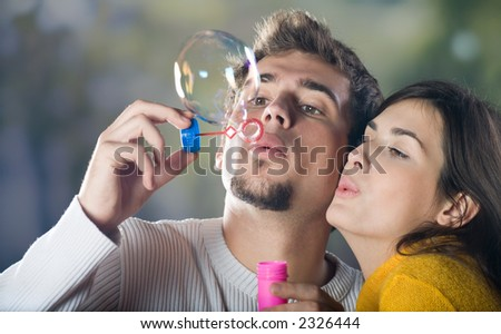 Young couple blowing bubbles, outdoors