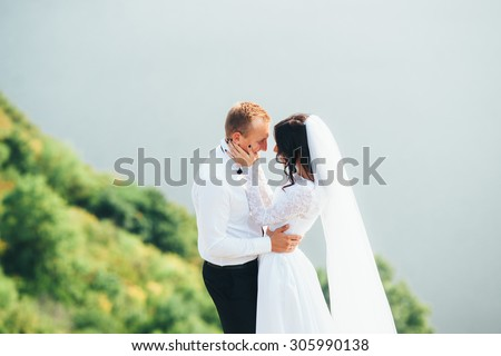 Young couple bride and groom outdoors against the backdrop of the beautiful nature. Newlyweds walking near the river