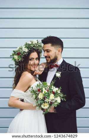 young couple bride groom getting married wedding posed photos at blue christian church hairpiece flowers bouquet