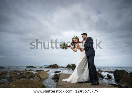 young couple bride groom getting married wedding posed photos at seaside sea beach hairpiece flowers bouquet