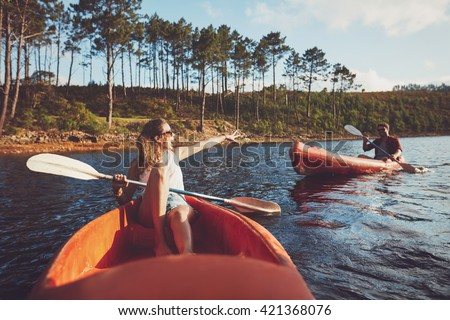 Young couple canoeing on the lake. Young kayakers enjoying a day at the lake.
