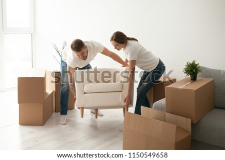 Young couple carry chair to new living room after moving in to shared apartment, husband and wife furnishing their first home, settling furniture, helping each other in renovation or interior design