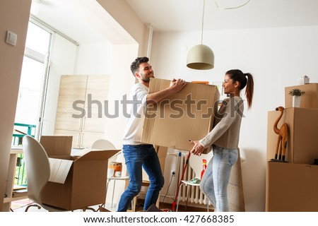 Young couple carrying big cardboard box at new home.Moving house. #427668385