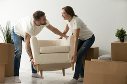 Young couple carrying chair together, house improvement, modern furniture in new home concept, man and woman moving into own flat after relocation furnishing living room, remodeling and renovation