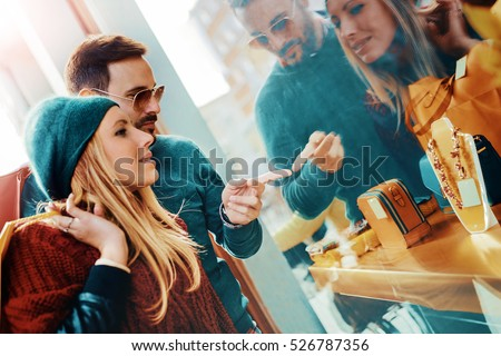 Young couple carrying shopping bags on shoulders and enjoying together in the city. Consumerism, shopping and lifestyle concept #526787356