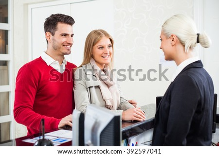 Young couple check in at hotel reception