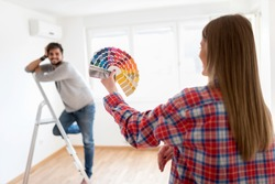 Young couple choosing color for painting home