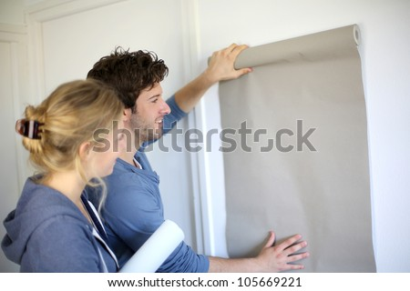Young couple choosing color of all paper in new home - stock photo