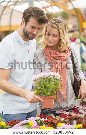 young couple choosing flowers in the garden center