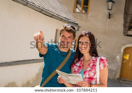Young couple city sightseeing man pointing direction woman hold map