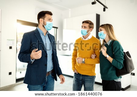 Young couple communicating with real estate agent while buying new home during coronavirus pandemic.  ストックフォト ©