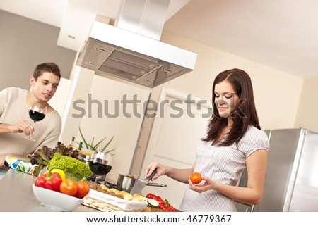 Young couple cooking in modern kitchen together - stock photo