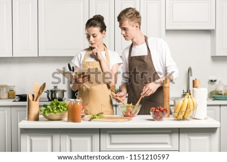 young couple cooking salad and reading recipe in cookbook in kitchen