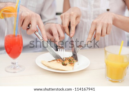 Young couple cutting a slice of pizza in cafe