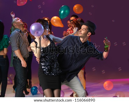 young couple dancing and looking at each other, in front of people patying in the background