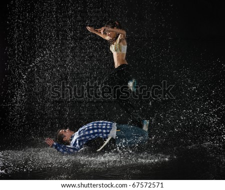 Young couple dancing in water under rain on a black background.  Modern dances. - stock photo
